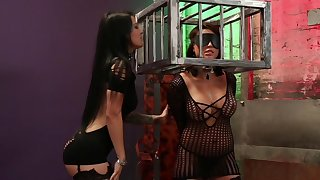 Caged woman plays submissive in lesbian BDSM